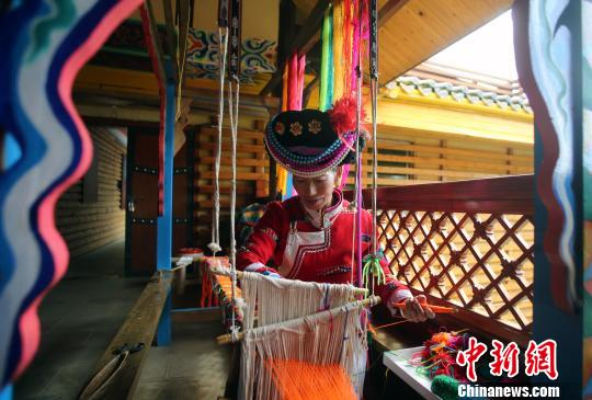 喇娜姆在编织花腰带。 王磊 摄